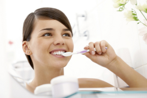 Woman brushing teeth during oral hugiene routine, as recommended by her San Carlos Dentist, Frank Hsu, DDS.